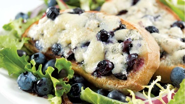 Sweet Ermite–blueberry crostini on a bed of greens