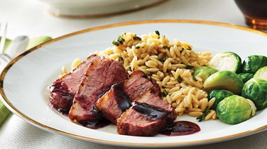 Duck breast with apricot red wine sauce & herb orzo