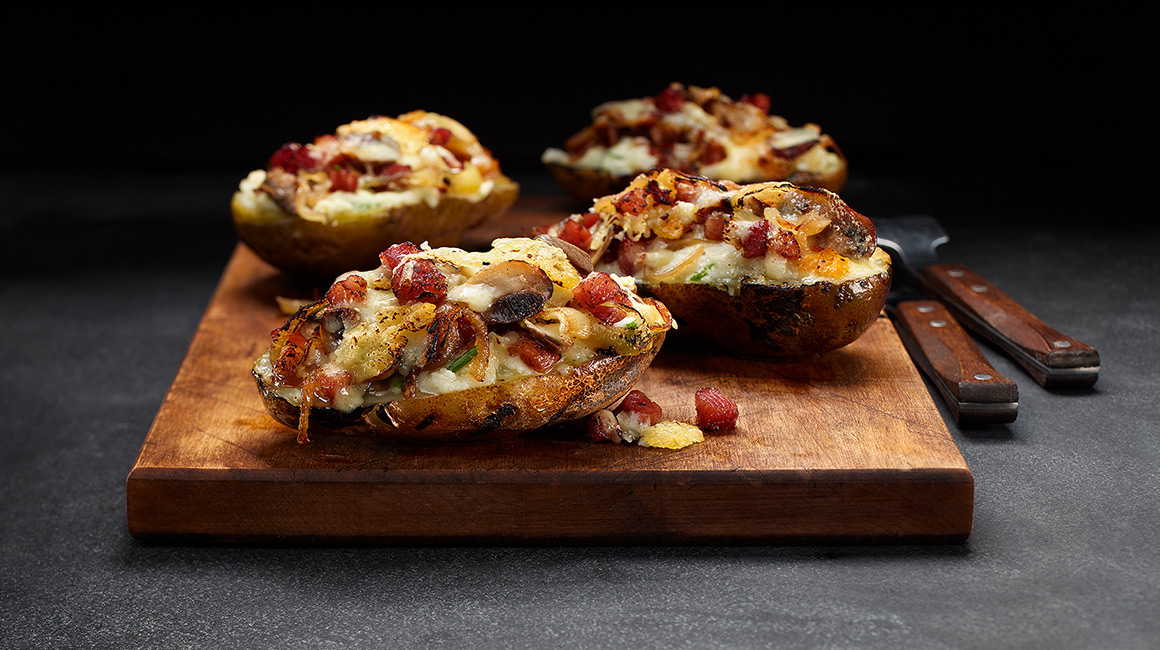 Baked Potatoes Stuffed with Mushrooms and Caramelized Onions Topped with Sharp Cheddar