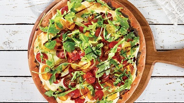 Pesto and colourful tomato pizza with fresh mozzarella