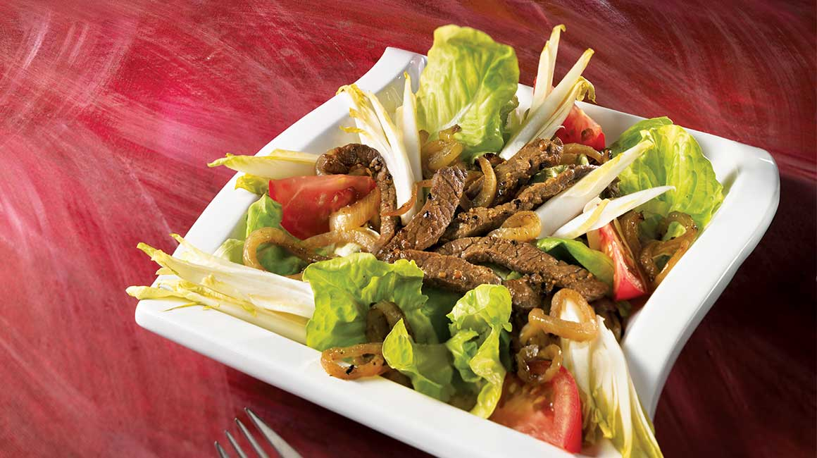Warm beef salad with black beer and caramelized onions